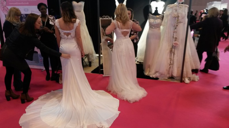 Brides trying on dresses at Estilo Moda Bridal Stand at The National Wedding Show Birmingham NEC